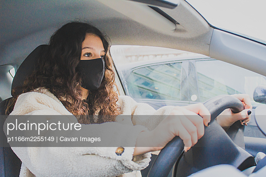 young woman driving with protective mask - p1166m2255149 by Cavan Images