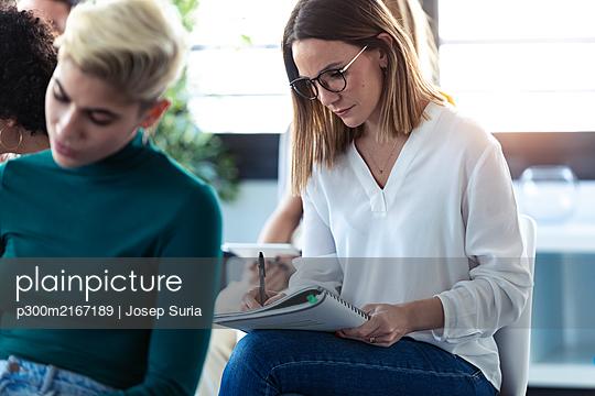 Businesswomen writing during a training - p300m2167189 by Josep Suria