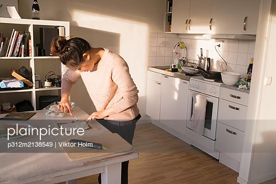 Woman preparing food in kitchen - p312m2138549 by Viktor Holm