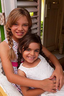 Zwei Schwestern sitzen auf Febsterbank - p045m2031205 von Jasmin Sander