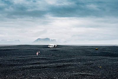 Mid distance view of siblings running towards wrecked airplane on black sand at beach against cloudy sky - p1166m2001350 by Cavan Images