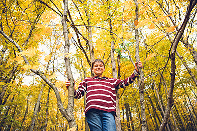 Low angle portrait of boy standing against maple tree in forest during autumn - p1166m2066419 by Cavan Images