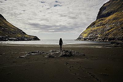Woman on the beach looks at the sea, Faroe Islands - p1239m2272818 by Krista Keltanen