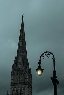 Atmospheric, mysterious dusk or night view of a cathedral spire and a single, lit, traditional street light. - p1433m1563439 by Wolf Kettler