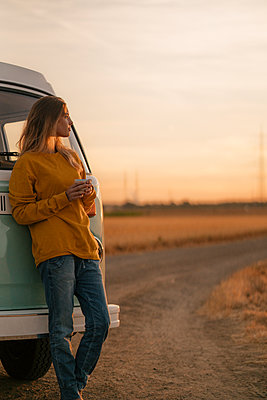 Young woman standing at camper van in rural landscape at sunset - p300m2058848 von Gustafsson
