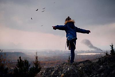 Caucasian girl balancing on rocks imitating flying birds - p555m1219679 by Vladimir Serov