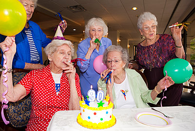 Older friends celebrating birthday in retirement home - p555m1408823 by Shestock