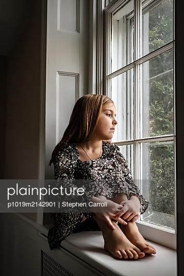 Mädchen sitzt auf der Fernsterbank - p1019m2142901 von Stephen Carroll