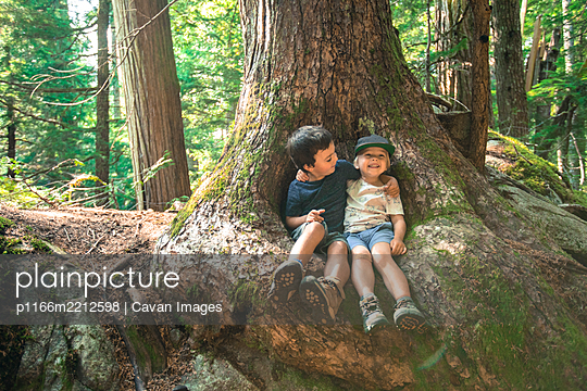 Two young boy friends embrace happily under large tree - p1166m2212598 by Cavan Images