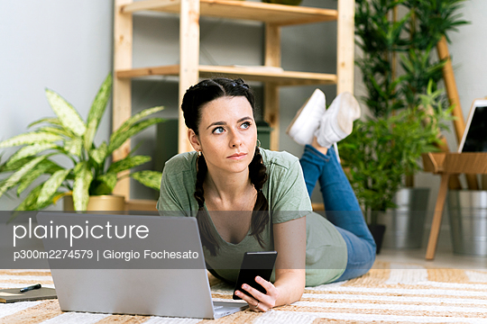 Contemplating woman holding smart phone by laptop while lying at home - p300m2274579 by Giorgio Fochesato