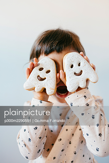 Little girl with mouth open covering eyes with ghost cookies - p300m2290551 by Gemma Ferrando