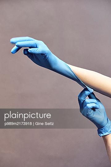 Gummihandschuhe anziehen - p989m2173918 von Gine Seitz