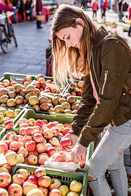Girl with cloth bag choosing apples on weekly market - p300m2103815 by Stefanie Baum