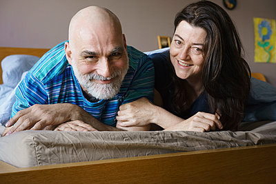 Portrait of happy mature couple lying on bed at home - p301m1130838f by Halfdark