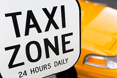 Taxi Zone parking sign with yellow cab in the background. - p343m1554651 by Ron Koeberer