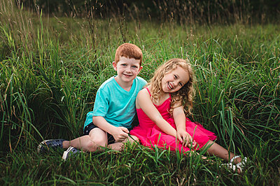Portrait of girl and brother sitting in field - p429m1504627 by Erin Lester