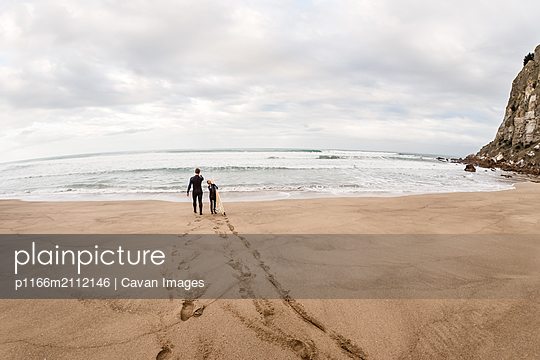 Man and girl walking to ocean with surfboard - p1166m2112146 by Cavan Images