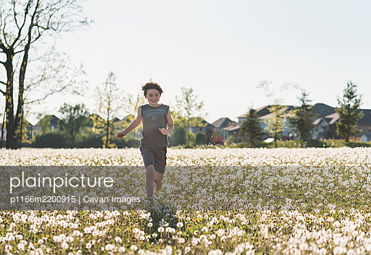 Boy running in a grassy field full of dandelions on summer day. - p1166m2200915 by Cavan Images