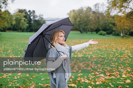 Junge Frau mit Regenschirm im Park - p586m971602 von Kniel Synnatzschke