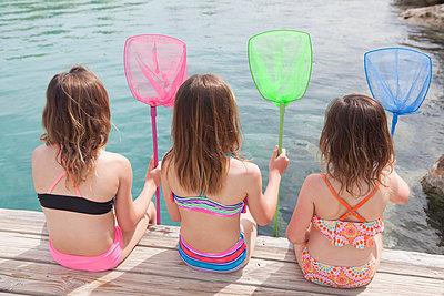 Drei Mädchen sitzen mit Catcher auf Steg - p045m1591422 von Jasmin Sander