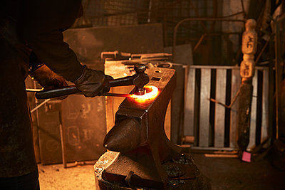 Blacksmith shaping steel on anvil in workshop - p1023m2200948 by Himalayan Pics