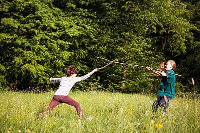 Jungen beim Stockkampf im Park - p1195m1138140 von Kathrin Brunnhofer