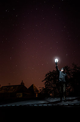 Man holding lamp in his hand - p1402m2177993 by Jerome Paressant