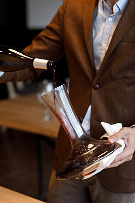 Waiter pouring red wine into decanter - p1427m2110160 by Mykhailo Lukashuk