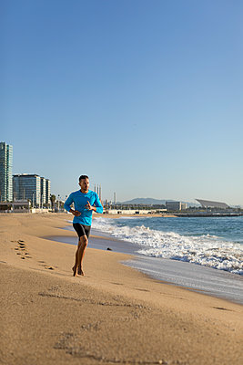 Man jogging on the beach - p300m2121493 by Mauro Grigollo