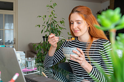 Young woman having breakfast and using laptop at desk at home - p300m2179965 by VITTA GALLERY