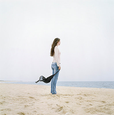Side profile of a young woman holding a scarf and standing on the beach - p3741531 by Karin Smeds