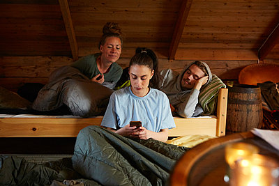 Friends looking at female using smart phone while relaxing on bed in cottage - p426m2117152 by Maskot