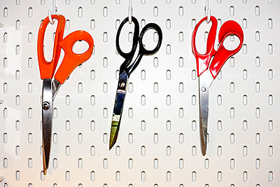 Three pairs of scissors hanging on a white pegboard - p1302m2245046 by Richard Nixon