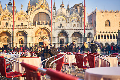 Man phoning in a sidewalk cafe on St. Mark's Square - p1312m2082189 by Axel Killian