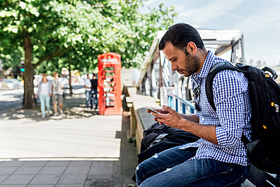 UK, London, man using his smartphone on the street - p300m2080957 by Marco Govel