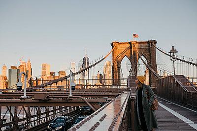USA, New York, New York City, female tourist on Brooklyn Bridge in the morning light - p300m2081047 by letizia haessig photography