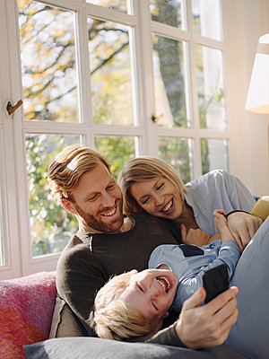 Happy family using cell phone in sunroom at home - p300m2205518 by Kniel Synnatzschke