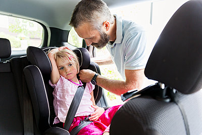 Father buckle girl in car - p312m1192829 by Susanne Kronholm