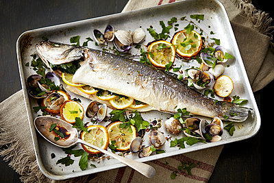 Baking tray with baked fish stuffed with lemon and herbs - p429m941129 by Debby Lewis-Harrison