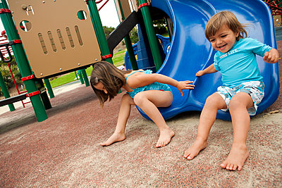 Brother and sister sliding down slide on playground - p555m1479293 by Jihan Abdalla