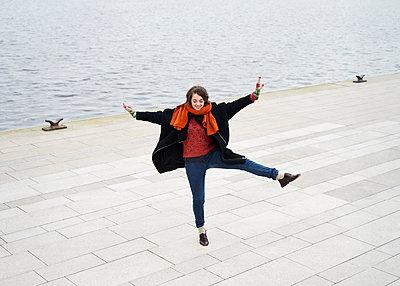 Junge Frau tanzt auf Promenade - p1124m1123280 von Willing-Holtz