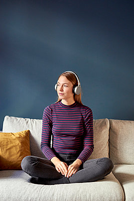 Young woman listens to music with headphones - p1124m1589228 by Willing-Holtz