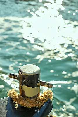 Bollard and rope in the sun - p1312m1575226 by Axel Killian