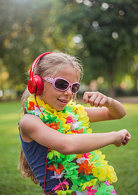 Cute girl in floral garland dancing while listening music through headphones at park - p300m2239982 by LOUIS CHRISTIAN