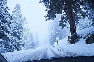 Windscreen view of snow covered rural forest road, Gstaad, Switzerland - p429m1418011 by Jakob Helbig