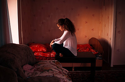 Caucasian woman sitting in bedroom - p555m1304649 by Marat Safin