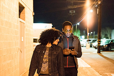 Couple walking in street at night looking at smartphone, Los Angeles, California, USA - p924m1422801 by Raphye Alexius