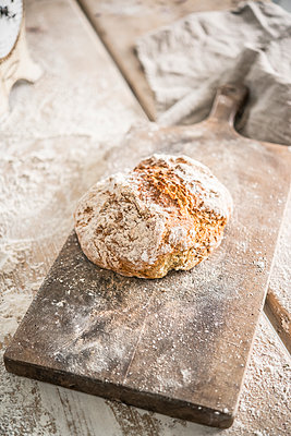 Loaf of bread on wooden board - p936m1161850 by Mike Hofstetter
