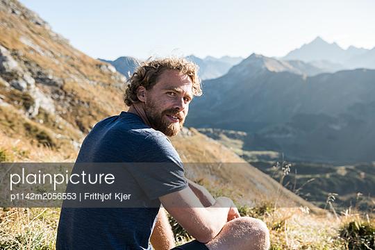 Junger Mann auf Wiese in den Bergen  - p1142m2056553 von Runar Lind