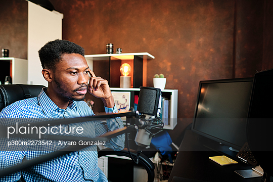 Thoughtful male influencer sitting on chair in front of computer at home - p300m2273542 by Alvaro Gonzalez